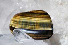 Tiger eye laid on druze of quartz. Tiger eye gem energized on druze of quartz crystals. This gem is used as a jewel stone and also in alternative medicine and Royalty Free Stock Photography