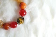 Tiger eye and various quartz lucky stone bracelet in red and white tone on white wool texture background. And have some space for write wording royalty free stock image