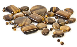 Tiger eyes. Tiger's eye gemstone beads in different shapes Stock Photography