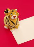 Tiger figurine on blank. Tiger statuette and blank on red background Stock Photos