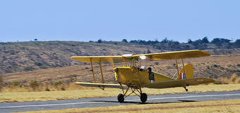 Tiger Moth - All Yellow. An all yellow colour scheme on this vintage bi-plane. Seen here taking part in a Spot Landing competition during an air show, held Stock Photos