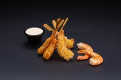 Tiger prawns in batter. Ebi tempura with spicy sauce on dark background. Fried shrimps stock image