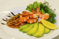 Tiger prawns with fruit and green. The delicious mediterranean tiger prawns with fruit and  green are on the white plate Stock Photo