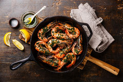 Tiger prawns on frying pan with green sauce Stock Photo