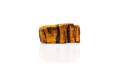 Tiger's eye gem stone rough isolated white. Background studio. Semi precious stone royalty free stock photo