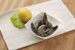 Tiger shrimps. Some raw tiger shrimps in the white bowl wit lemon and lettuce Royalty Free Stock Image