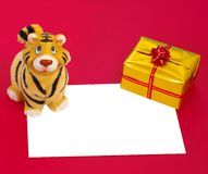 Tiger statuette,present box and blank. Tiger figurine,form and  present box in gold wrap on red background Stock Photography