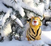 Tiger symbol of 2010 year. Statuette tiger on snow-bound fir-tree Royalty Free Stock Photo