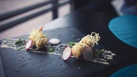Tigerräkor i kinesiska nudlar med sås på den svarta plattan Asiatisk matbakgrund Äta begrepp Restaurangställe med träta Royaltyfri Fotografi