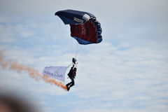 Tigers parachute display team at Bournemouth airshow 2015. Parachutist  coming into land with an orange smoke trail and flag suspended beneath him Stock Images