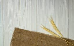 Tiges et toile à sac de blé sur le fond en bois blanc Photographie stock libre de droits
