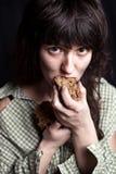 Tiggarekvinna som äter bröd royaltyfri bild