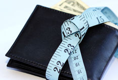 Tight Budget. Conceptual photo of a tight budget showing a man's wallet with a dollar bills sticking out and tied with a measuring tape Royalty Free Stock Image