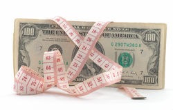 Tight budgeting. Unravel tape on side. Measuring tape over money, budgeting, measure money, tight budget. Unravelled tape on side. Messy royalty free stock images