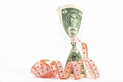 Tight budgeting. Upright money. Measuring tape over money, budgeting, measure money, tight budget. Money upright. Could also signify expensive slimming royalty free stock image
