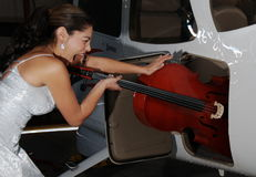 Tight Cello. Beautiful woman trying to figure out how to load a cello into a light airplane baggage compartment Royalty Free Stock Photo