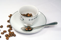 Tight closeup of espresso cup and saucer with beans. Closeup shot of an espresso cup with scattered coffee beans, saucer and spoon. Shot in studio light on a Stock Photography