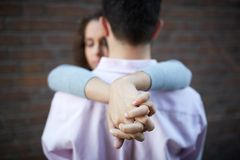 Tight embrace. Conceptual image of female hands while embracing her sweetheart Stock Photos