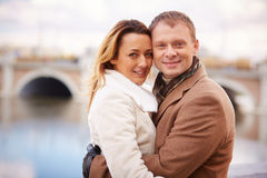 Tight embrace. Portrait of smiling dates embracing and looking at camera in urban environment Stock Images