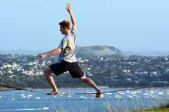 Tight rope walking. AUCKLAND, NZ - JAN 18:Young man walk on a rope on Jan 18 2014. Tight rope walking has been around at least two thousand years originated in Royalty Free Stock Photography