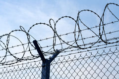 Tight security. Razor wire atop of a barbed wire secure fence Royalty Free Stock Image
