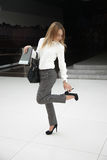 Tight shoes. Beautiful young woman in office style white shirt holding black document folder and leather bag, touching her high heel shoe, feeling uncomfortable Royalty Free Stock Images