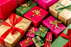 Tight Shot Brimming Over With Gifts. Plenty of wrapped presents in plain red, green, gold and magenta filling the frame. Shallow depth of field. Fit for any gift Royalty Free Stock Photography