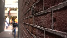 Tight Side Street Passage in Center of Amsterdam, Netherlands. Red bricks wall and Crowded Shopping street on background stock video