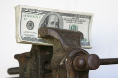 Tight squeeze. American cash held tightly in a vice with a white background royalty free stock image