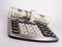 Tighten Budget Calculator. Calculator with US $20 bills wrapped with a measuring tape royalty free stock photo