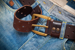 Tighten the leather belt with a buckle on jeans Royalty Free Stock Photos