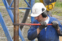 Tighten that pipe. Drilling crewman tightens pipe on drillstring Stock Image