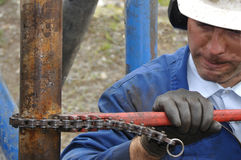 Tighten that pipe. Drilling crewman tightens pipe on drillstring Stock Images