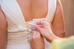 Tighten wedding dress on bride. Tighten wedding gown on bride Stock Images