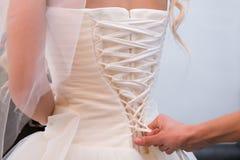 Tighten wedding dress on bride. Tighten wedding gown on bride Royalty Free Stock Images