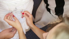 Tightened bride corset. On white wedding elegant dress