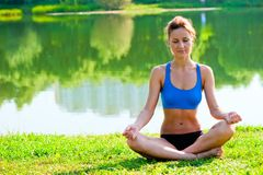Tightened girl in sportswear meditating in the lotus position at the lake Royalty Free Stock Photo