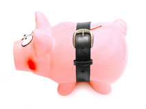Tightening the belt. Piggy bank with a belt wrapped around its shrinking body Royalty Free Stock Photos