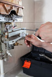 Tightening bolt on gas water heater Royalty Free Stock Photography