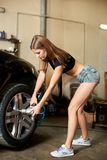 Tightening the bolts of a black sport car. Performed by a model Royalty Free Stock Image