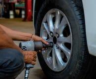 Tightening bolts of car wheel. Royalty Free Stock Photos