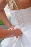 Tightening brides corset. Assistant girl tightening brides white corset. Vertical shot Royalty Free Stock Image