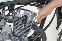 Tightening exhaust. Mechanic tightening the exhaust on a motorcycle engine Royalty Free Stock Photography