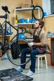 Tightening handlebars. Owner of bike repair workshop fixing handlebars of bicycle Stock Image