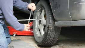 Replacing nuts on tire. Tightening nuts on tire in garage stock video footage