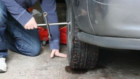 Spinning wrench in garage 2. Tightening nuts on tire in garage stock footage