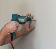 Tightening the screw in the drywall. Construction and installation work on plasterboard walls Royalty Free Stock Photos