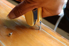 Tightening the screw by mag stapler to fix the problem. Tightening the screw by mag stapler to fix the problem on the table Stock Photo