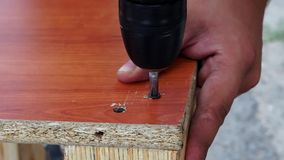 Tightening the screws closeup of electric screwdriver. Twists the screws with an electric drill close-up. Repair work on wood furniture collection stock footage