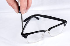 Tightening the small screw on a pair of glasses. Eye glasses get a repair on a white surface Stock Photo